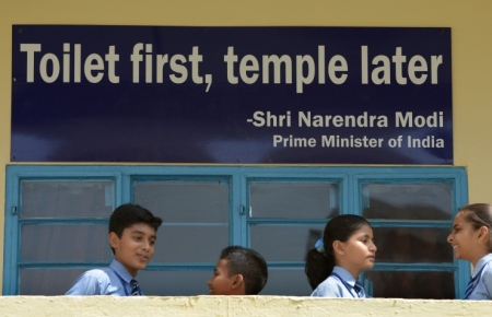 TO GO WITH India-sanitation-social-toilet-Gandhi,FOCUS BY ABHAYA SRIVASTAVA  In this photograph taken on September 22, 2014, Indian schoolchildren talk in front of a poster bearing a quote from Prime Minister Narendra Modi at a school run by sanitation charity Sulabh International in New Delhi. Surrounded by latrines and soap dispensers, charity founder Bindeshwar Pathak is most at home in the toilet, one of which he vows to build in every impoverished home in India.  AFP PHOTO/SAJJAD HUSSAIN        (Photo credit should read SAJJAD HUSSAIN/AFP/Getty Images)