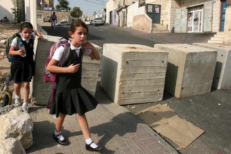 Palestinian school girls walk between cement blocks at a newly erected checkpoint in Jerusalem's neighborhood of Jabal al-Mokaber